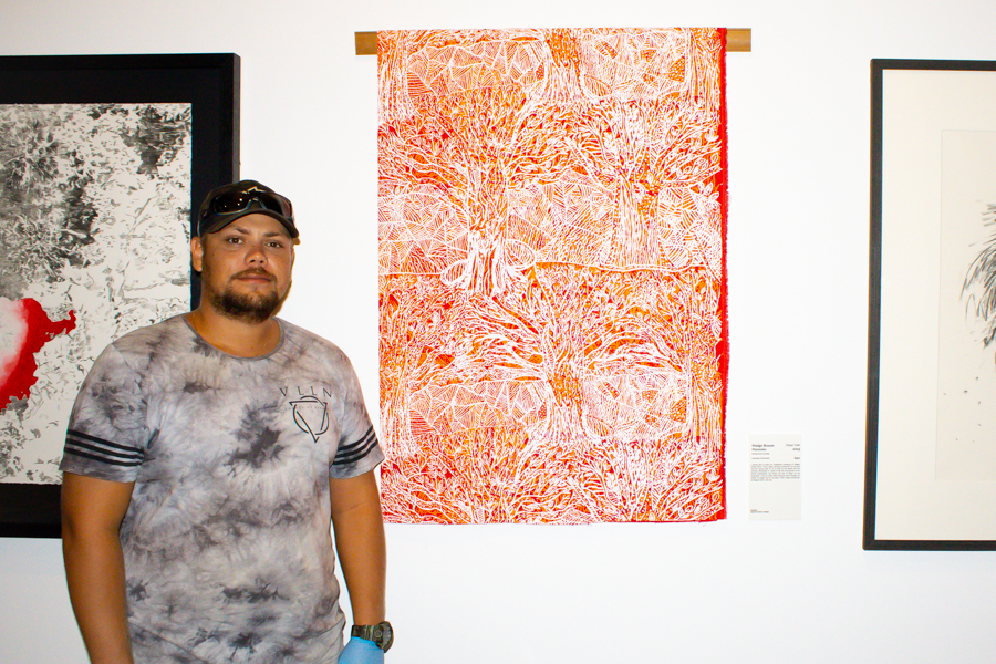 Jaivan is smiling next to an artwork made by his grandmother Madge Bowen. The artwork is an intricate red, orange and white screen print.